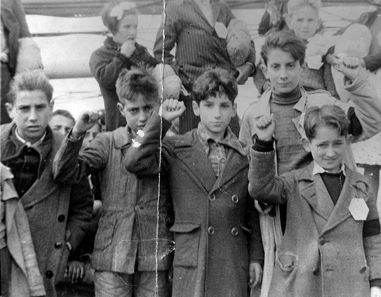 Des enfants se préparant à l'exil d'Espagne entre 1936 et 1939, levant le poing en signe d'attachement aux Républicains.